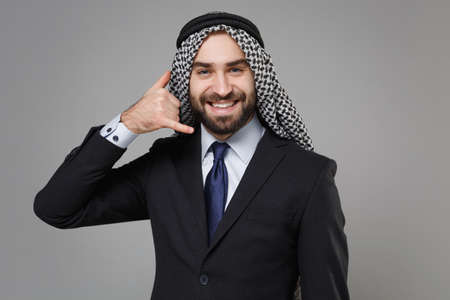 Smiling arabian muslim businessman in keffiyeh kafiya ring igal agal classic black suit isolated on gray background. Achievement career wealth business concept. Doing phone gesture says call me back. Standard-Bild