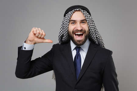 Laughing bearded arabian muslim businessman in keffiyeh kafiya ring igal agal classic black suit tie isolated on gray background. Achievement career wealth business concept. Pointing thumb on himself. Banco de Imagens - 156217591