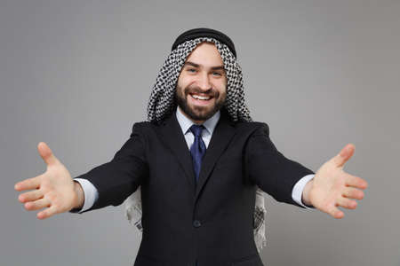 Smiling bearded arabian muslim businessman in keffiyeh kafiya ring igal agal classic black suit isolated on gray background. Achievement career wealth business concept. Stand with outstretched hands.