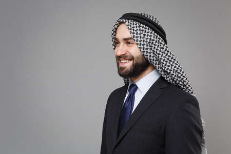 Smiling young bearded arabian muslim businessman in keffiyeh kafiya ring igal agal classic black suit shirt tie isolated on gray background. Achievement career wealth business concept. Looking aside. Standard-Bild