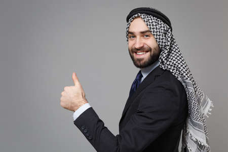 Side view of smiling arabian muslim businessman in keffiyeh kafiya ring igal agal classic black suit shirt tie isolated on gray background. Achievement career wealth business concept Showing thumb up. Banco de Imagens - 156217594