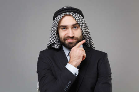 Confused bearded arabian muslim businessman in keffiyeh kafiya ring igal agal classic black suit shirt isolated on gray background. Achievement career wealth business concept Put hand prop up on chin.