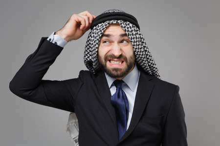 Puzzled young bearded arabian muslim businessman in keffiyeh kafiya ring igal agal classic black suit shirt isolated on gray background. Achievement career wealth business concept. Put hand on head. Standard-Bild