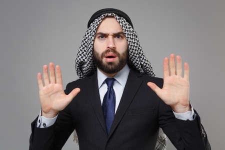 Perplexed bearded arabian muslim businessman in keffiyeh kafiya ring igal agal classic black suit isolated on gray background. Achievement career wealth business concept. RIsing hands, showing palms.