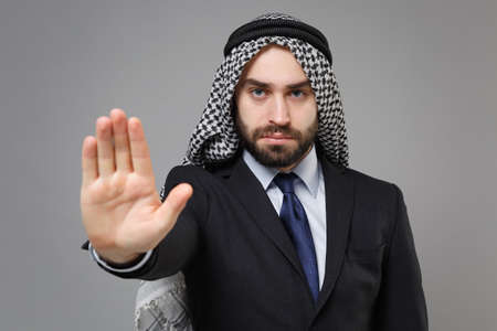 Serious bearded arabian muslim businessman in keffiyeh kafiya ring igal agal classic black suit isolated on gray background. Achievement career wealth business concept. Showing stop gesture with palm.