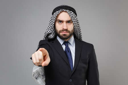 Strict bearded arabian muslim businessman in keffiyeh kafiya ring igal agal classic black suit isolated on gray background. Achievement career wealth business concept. Pointing index finger on camera.