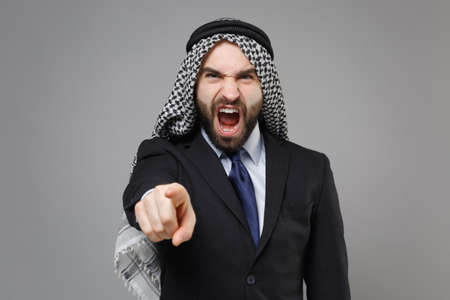 Angry arabian muslim businessman in keffiyeh kafiya ring igal agal classic black suit isolated on gray background. Achievement career wealth business concept. Pointing index finger on camera swearing.