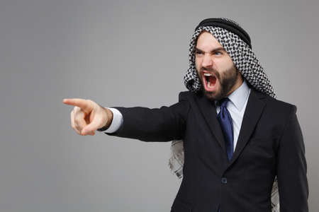 Irritated arabian muslim businessman in keffiyeh kafiya ring igal agal classic black suit isolated on gray background. Achievement career wealth business concept. Pointing index finger aside swearing. Banco de Imagens
