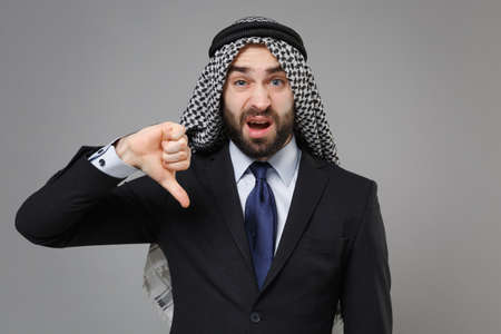Displeased bearded arabian muslim businessman in keffiyeh kafiya ring igal agal classic black suit shirt isolated on gray background. Achievement career wealth business concept. Showing thumb down.