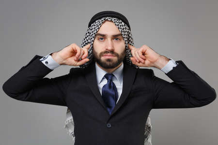 Young bearded arabian muslim businessman in keffiyeh kafiya ring igal agal classic black suit shirt isolated on gray background. Achievement career wealth business concept. Covering ears with fingers.