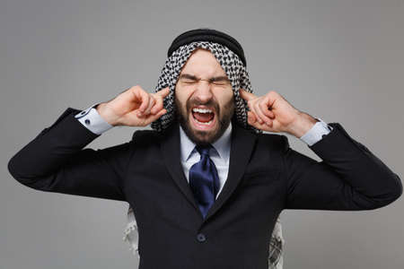 Crazy arabian muslim businessman in keffiyeh kafiya ring igal agal classic black suit tie isolated on gray background. Achievement career wealth business concept. Covering ears with fingers screaming.