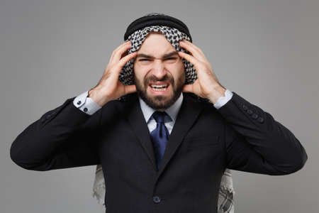 Sick young bearded arabian muslim businessman in keffiyeh kafiya ring igal agal classic black suit shirt tie isolated on gray background. Achievement career wealth business concept. Put hands on head. Standard-Bild