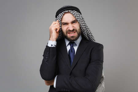 Concerned young bearded arabian muslim businessman in keffiyeh kafiya ring igal agal classic black suit shirt isolated on gray background. Achievement career wealth business concept. Put hand on head.