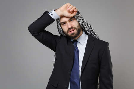 Tired young bearded arabian muslim businessman in keffiyeh kafiya ring igal agal classic black suit shirt tie isolated on gray background. Achievement career wealth business concept. Put hand on head. Standard-Bild