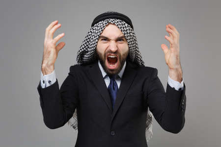 Angry bearded arabian muslim businessman in keffiyeh kafiya ring igal agal classic black suit shirt isolated on gray background. Achievement career wealth business concept. Screaming spreading hands.