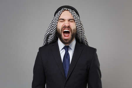 Frustrated arabian muslim businessman in keffiyeh kafiya ring igal agal classic black suit shirt isolated on gray background. Achievement career wealth business concept. Screaming keeping eyes closed.