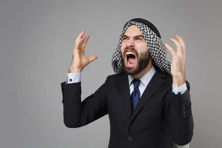 Angry bearded arabian muslim businessman in keffiyeh kafiya ring igal agal classic black suit shirt isolated on gray background. Achievement career wealth business concept. Swearing spreading hands. Banco de Imagens