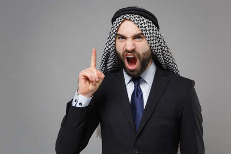 Angry bearded arabian muslim businessman in keffiyeh kafiya ring igal agal classic black suit shirt isolated on gray background. Achievement career wealth business concept. Swearing point finger up. Standard-Bild