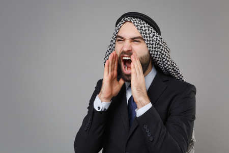 Crazy bearded arabian muslim businessman in keffiyeh kafiya ring igal agal classic black suit shirt isolated on gray background. Achievement career wealth business concept. Scream with hands gesture. Banco de Imagens