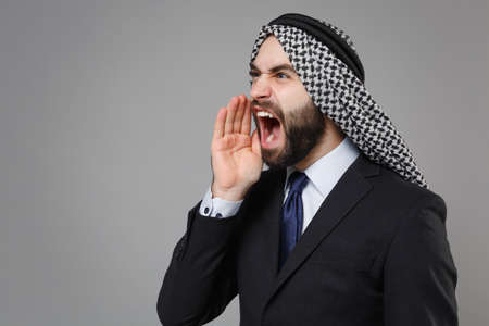 Angry bearded arabian muslim businessman in keffiyeh kafiya ring igal agal classic black suit shirt isolated on gray background. Achievement career wealth business concept. Scream with hand gesture.