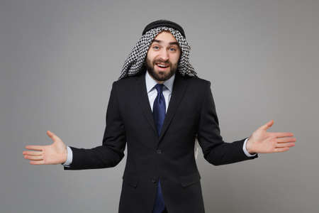 Perplexed young bearded arabian muslim businessman in keffiyeh kafiya ring igal agal classic black suit shirt isolated on gray background. Achievement career wealth business concept. Spreading hands. Standard-Bild