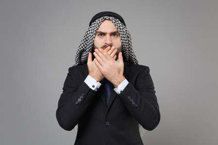 Shocked young bearded arabian muslim businessman in keffiyeh kafiya ring igal agal black suit shirt isolated on gray background. Achievement career wealth business concept. Covering mouth with hands. Standard-Bild