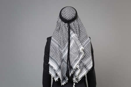 Back rear view of young arabian muslim businessman in keffiyeh kafiya ring igal agal classic black suit isolated on gray wall background studio portrait. Achievement career wealth business concept. Banco de Imagens