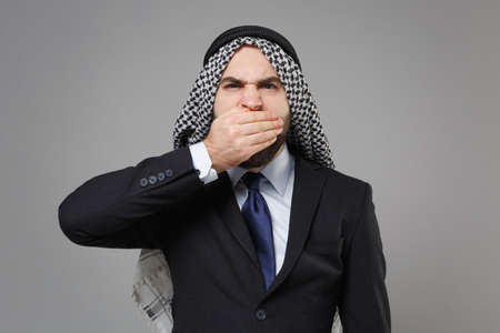 Displeased arabian muslim businessman in keffiyeh kafiya ring igal agal classic black suit shirt isolated on gray background. Achievement career wealth business concept. Covering mouth with hands. Banco de Imagens