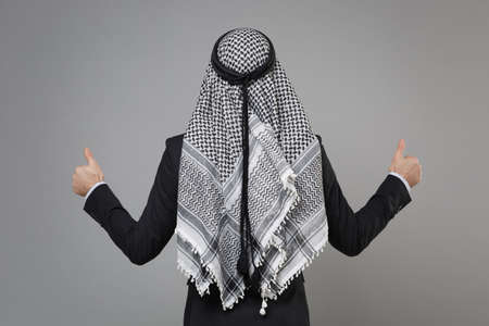 Back rear view of young arabian muslim businessman in keffiyeh kafiya ring igal agal classic black suit isolated on gray wall background. Achievement career wealth business concept. Showing thumbs up.