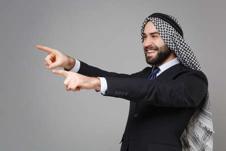 Funny bearded arabian muslim businessman in keffiyeh kafiya ring igal agal classic black suit shirt isolated on gray background. Achievement career wealth business concept. Point index fingers aside.
