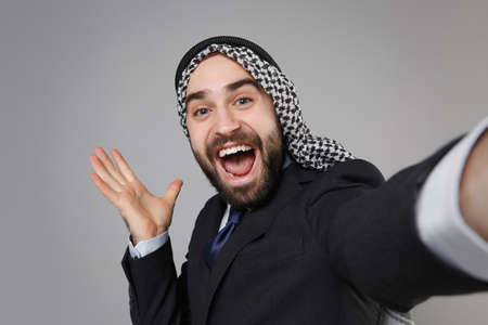 Close up of arabian muslim businessman in keffiyeh kafiya ring igal agal black suit isolated on gray background. Achievement career wealth business. Doing selfie shot on mobile phone spreading hands.