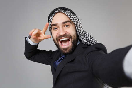 Close up of arabian muslim businessman in keffiyeh kafiya ring igal agal suit isolated on gray background. Achievement career wealth business. Doing selfie shot on mobile phone showing victory sign.