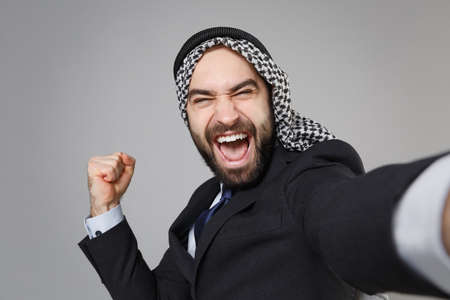 Close up of arabian muslim businessman in keffiyeh kafiya ring igal agal suit isolated on gray background. Achievement career wealth business. Doing selfie shot on mobile phone doing winner gesture.