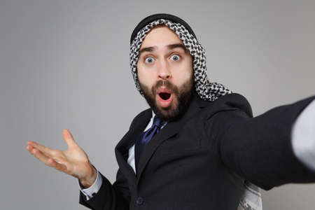 Close up of arabian muslim businessman in keffiyeh kafiya ring igal agal suit isolated on gray background. Achievement career wealth business. Doing selfie shot on mobile phone keeping mouth open. Banco de Imagens