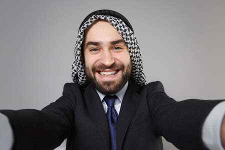 Close up of smiling arabian muslim businessman in keffiyeh kafiya ring igal agal black suit isolated on gray background. Achievement career wealth business concept. Doing selfie shot on mobile phone.