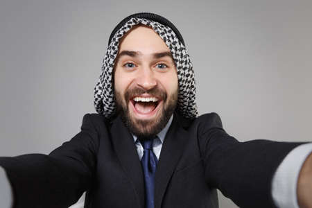 Close up of cheerful arabian muslim businessman in keffiyeh kafiya ring igal agal black suit isolated on gray background. Achievement career wealth business concept. Doing selfie shot on mobile phone.