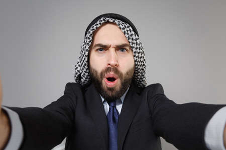 Close up of shocked arabian muslim businessman in keffiyeh kafiya ring igal agal black suit isolated on gray background. Achievement career wealth business concept. Doing selfie shot on mobile phone.