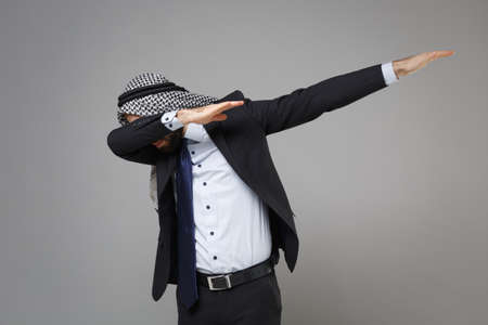Cheerful bearded arabian muslim businessman in keffiyeh kafiya ring igal agal classic black suit isolated on gray background. Achievement career wealth business concept. Showing DAB dance gesture.