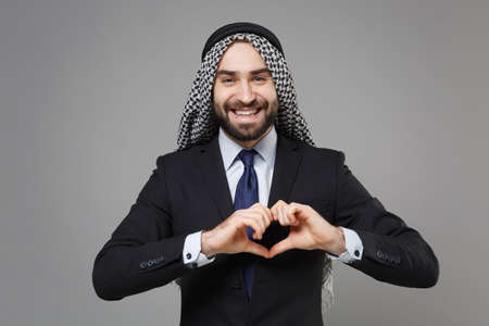 Smiling bearded arabian muslim businessman in keffiyeh kafiya ring igal agal classic black suit isolated on gray background. Achievement career wealth business concept. Showing shape heart with hands.