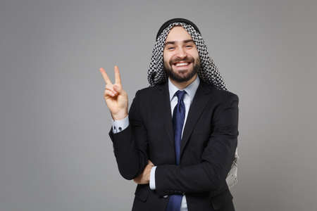 Smiling young bearded arabian muslim businessman in keffiyeh kafiya ring igal agal classic black suit tie isolated on gray background. Achievement career wealth business concept. Showing victory sign.