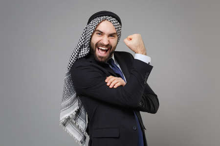 Funny young bearded arabian muslim businessman in keffiyeh kafiya ring igal agal classic black suit tie isolated on gray background. Achievement career wealth business concept. Showing biceps muscles.