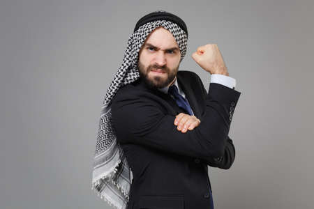 Strong young bearded arabian muslim businessman in keffiyeh kafiya ring igal agal classic black suit isolated on gray background. Achievement career wealth business concept. Showing biceps, muscles. Banco de Imagens