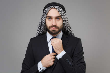 Young bearded arabian muslim businessman in keffiyeh kafiya ring igal agal classic black suit shirt isolated on gray wall background. Achievement career wealth business concept. Straightening tie.