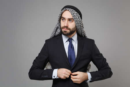 Handsome young bearded arabian muslim businessman in keffiyeh kafiya ring igal agal classic black suit shirt isolated on gray background. Achievement career wealth business concept. Fastening jacket.