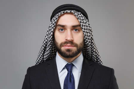 Handsome young bearded arabian muslim businessman in keffiyeh kafiya ring igal agal classic black suit shirt tie isolated on gray background. Achievement career wealth business concept Looking camera.