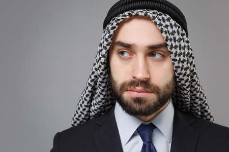 Close up of young bearded arabian muslim businessman in keffiyeh kafiya ring igal agal classic black suit shirt isolated on gray background. Achievement career wealth business concept. Looking aside.