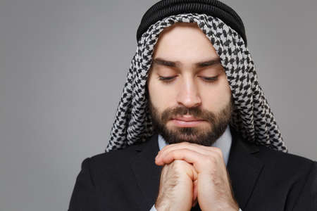 Close up of bearded arabian muslim businessman in keffiyeh kafiya ring igal agal classic suit isolated on gray background. Achievement career wealth business concept. Holding hands folded in prayer. Banco de Imagens