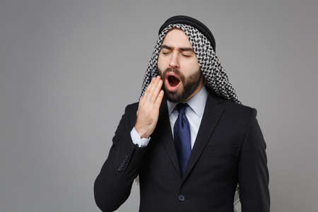 Tired young bearded arabian muslim businessman in keffiyeh kafiya ring igal agal classic suit isolated on gray background. Achievement career wealth business concept. Yawning covering mouth with hand.