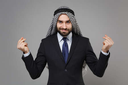 Arabian muslim businessman in keffiyeh kafiya ring igal agal classic suit isolated on gray background. Achievement career wealth business concept. Rubbing fingers showing cash gesture ask for money.