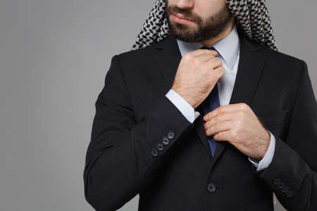 Cropped image of bearded arabian muslim businessman in keffiyeh kafiya ring igal agal classic black suit isolated on gray background. Achievement career wealth business concept. Straightening tie.